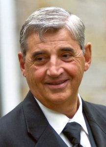 White-haired man wearing suit and tie smiles