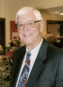 Man wearing glasses and a dark suit and tie