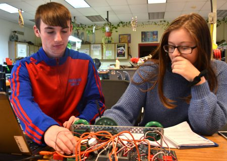 Two students work together on a project with wires