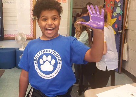 student with painted purple hand