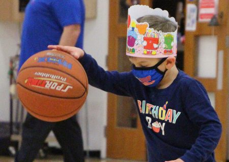 young boy with a birthday hat bouncing a ball