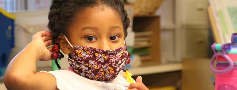 young African-American girl in class wearing a protective mask